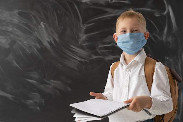 Een slimme schooljongen staat bij het schoolbord. er zit een beschermend masker op zijn gezicht. in de handen van de jongen is een groot notitieboekje om op te schrijven. scholing en sociale afstand.
