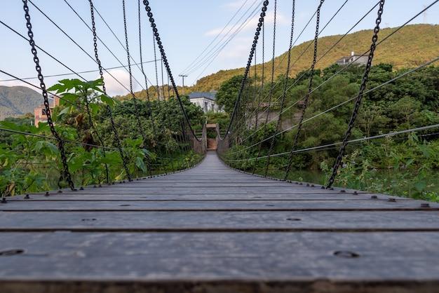 Een slingerbrug over een landelijke rivier