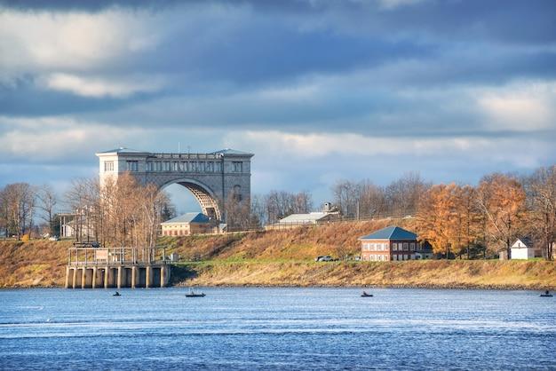 Een sluis voor schepen op de rivier in uglich en vissersboten in de stralen van de herfstzon