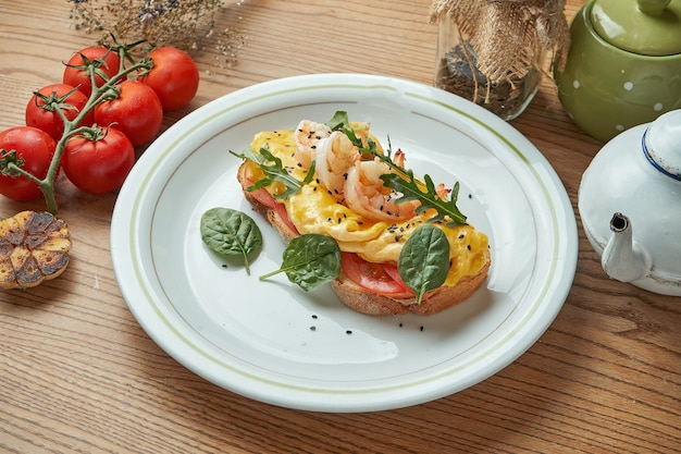 Een smakelijk en stevig ontbijt - een sandwich met roerei, garnalen, tomaten en hollandaisesaus, geserveerd in een witte plaat op een houten tafel. restaurant eten