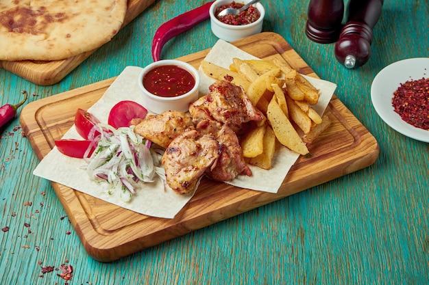 Een smakelijk oosters gerecht - gegrilde kip of rundvlees kebab met een bijgerecht van aardappelen en uien met rode uien op een groene tafel. georgische keuken. shish kebab