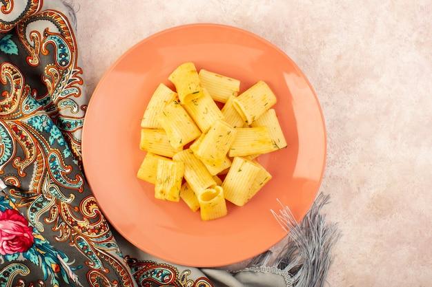 Een smakelijke maaltijd van bovenaanzicht italiaanse pasta met gedroogde groene kruiden in roze plaat op kleurrijke sjaal en roze