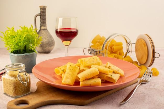 Een smakelijke maaltijd van vooraanzicht italiaanse deegwaren binnen roze plaat samen met bloem en ruwe deegwaren op roze