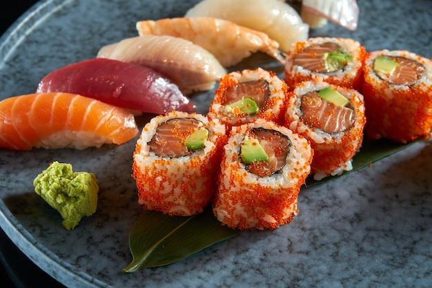 Een smakelijke sushi set bestaande uit verschillende nigiri en uramaki met zalm, avocado en tobiko kaviaar. japanse traditionele keuken. voedsellevering. geïsoleerd op zwart