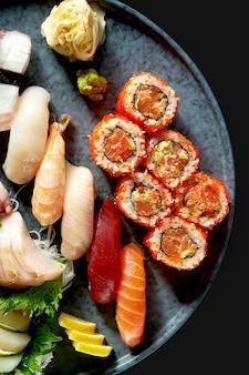 Een smakelijke sushi set bestaande uit verschillende nigiri. sashimi en uramaki met zalm, avocado en tobiko-kaviaar. japanse traditionele keuken. voedsellevering. geïsoleerd op zwart