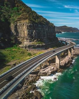 Een smalle bochtige weg met auto's langs groene bergen