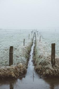 Een smalle waterweg in een mistig veld