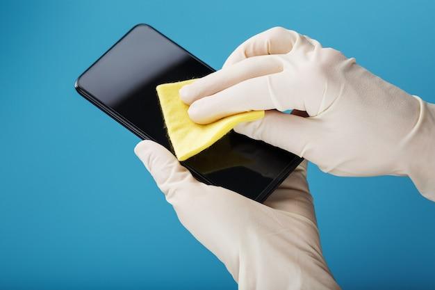 Een smartphone schoonmaken met een steriel geel servet in rubberen handschoenen op een blauwe achtergrond.