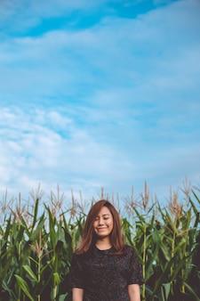 Een smiley aziatische vrouw sloot haar ogen en stond op de voorkant van maïsveld
