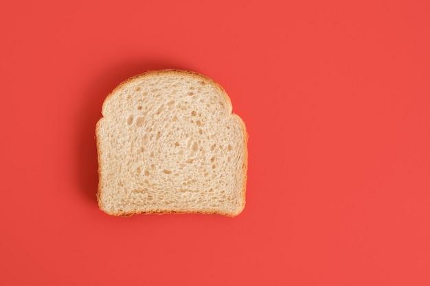 Een sneetje brood geïsoleerd op rood
