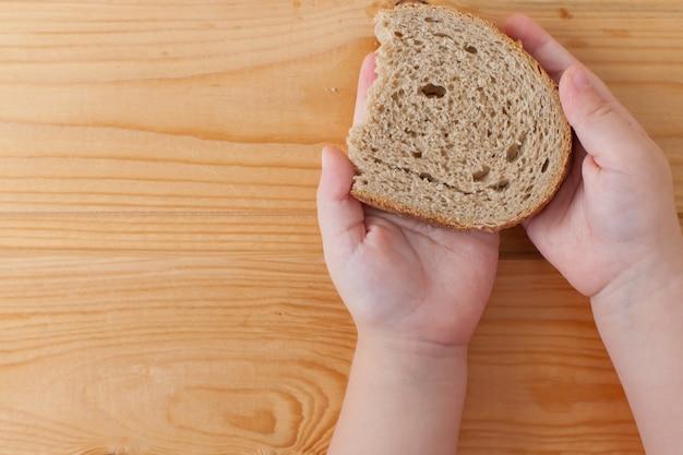 Een sneetje droog brood in kinderhanden. voedsel.
