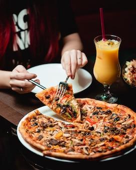 Een sneetje pizza met gemengd ingrediënt nemen met een glas sinaasappelsap.