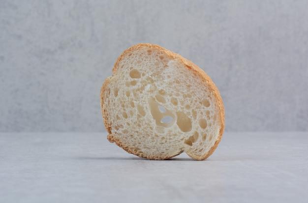 Een sneetje rond vers wit brood op marmeren achtergrond.
