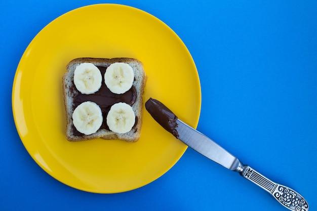 Een sneetje toastbrood met chocoladeroom en banaan in de gele plaat op de blauwe achtergrond.