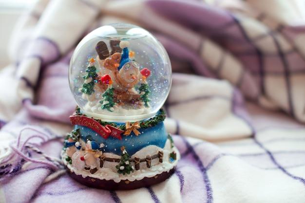 Een sneeuwbol met een sneeuwpop staat op een plaid