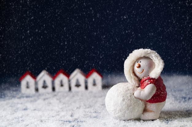 Een sneeuwpop rolt een sneeuwbal op de achtergrond van kleine huisjes op een donkerblauwe achtergrond