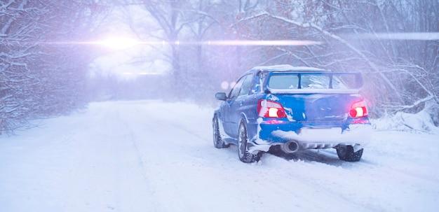 Een snelle blauwe sportwagen op besneeuwde winterdag, koud seizoen, straatweg