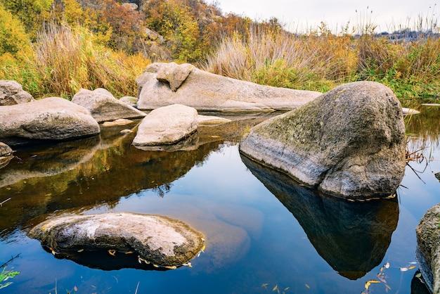 Een snelle, ondiepe, schone stroom stroomt tussen gladde, natte grote stenen omgeven door hoge droge brokken