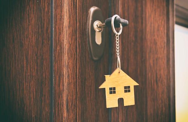 Een snuisterij in de vorm van een huis op de sleutel in het sleutelgat