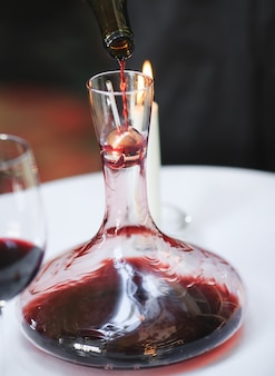 Een sommelier die rode wijn in karaf giet