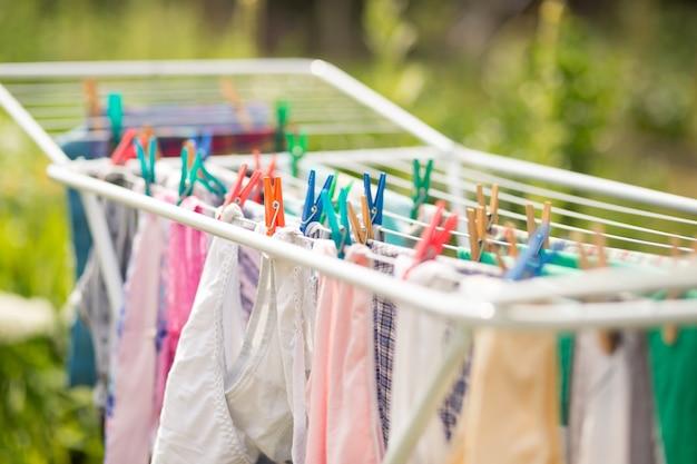 Een soort verschillende kleren die aan een droger hangen die door kleurrijke pinnen wordt bevestigd
