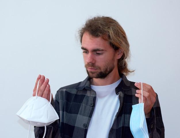 Een spaanse jonge man met een baard die twee soorten beschermende gezichtsmaskers vasthoudt en denkt welke hij moet dragen
