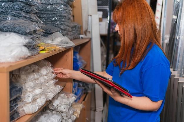 Een spaanse jonge vrouw die een inventaris van een blauw overhemd draagt die met behulp van een tablet in een magazijn controleert