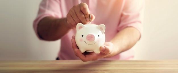 Een spaarvarken dat met hand geldmuntstuk op houten achtergrond zet. een besparing voor toekomstig investeringsconcept.