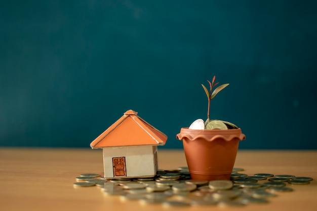 Een spaarvarken zet op de stapelen gouden munten en schoolbord huis