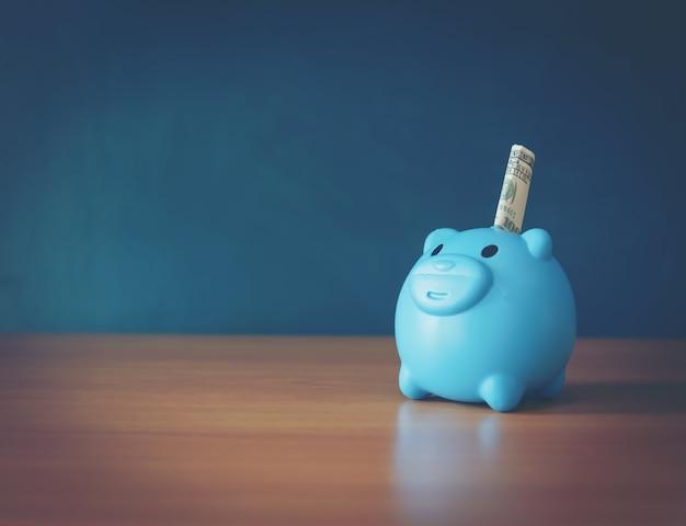 Een spaarvarken zette op de stapelende gouden muntstukken en het bordhuis en de klok op de uitstekende blauwe achtergrond, besparingsgeld voor een nieuwe onroerende goederen of een lening voor geplande investering in het toekomstige concept.