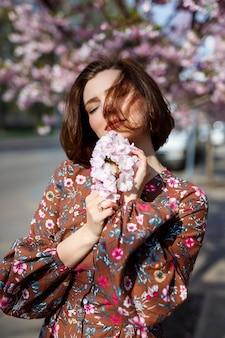 Een spectaculaire vrouw in een lichte jurk staat tegen de achtergrond van sakura. een donkerharige vrouw in een mooie outfit lacht op straat tijdens het wandelen