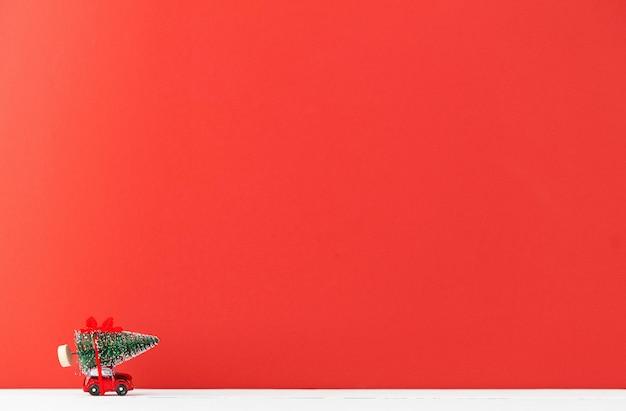 Een speelgoedauto draagt een kerstboom