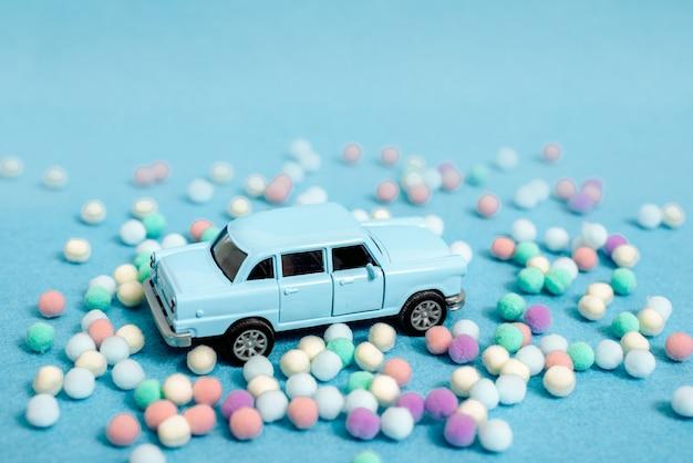 Een speelgoedauto rijdt in een kerstboom. op een blauwe achtergrond.