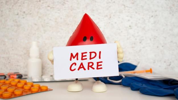 Een speelgoeddruppel bloed houdt een witte papieren kaart vast met het opschrift medi care. medisch concept.