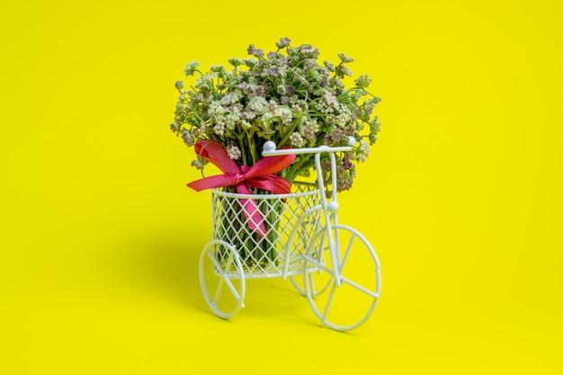 Een speelgoedfiets draagt bloemen. het idee voor een ansichtkaart. geel minimalisme.