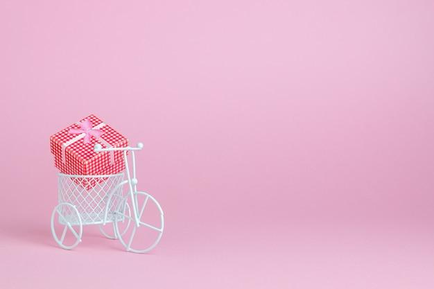 Een speelgoedfiets draagt een geschenk. het idee voor een ansichtkaart.