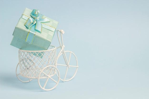 Een speelgoedfiets draagt een geschenk.
