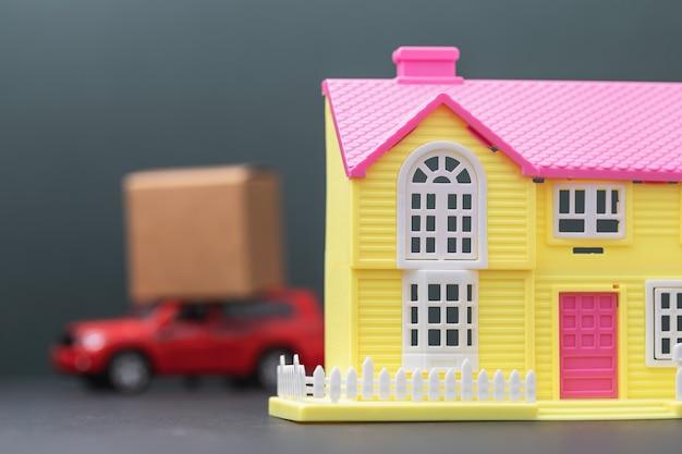 Een speelgoedhuis en een auto met een lading op het dak