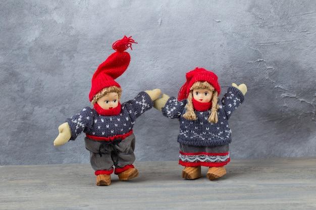 Een speelgoedjongen en -meisje in winterkleren houden elkaars hand vast