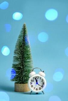 Een speelgoedkerstboom en een wekker die bijna middernacht aangeeft. kerstmissamenstelling met een kerstboom en een klok op een blauwe achtergrond met feestelijke hoogtepunten en exemplaarruimte.