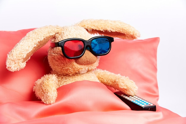 Een speelgoedkonijn in stereoglazen met een afstandsbediening van de tv ligt in bed.