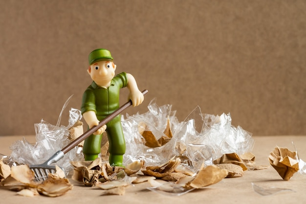 Een speelgoedman in een arbeiderspak harkt een grote hoeveelheid afval bij elkaar. milieubescherming en ecologie concept.
