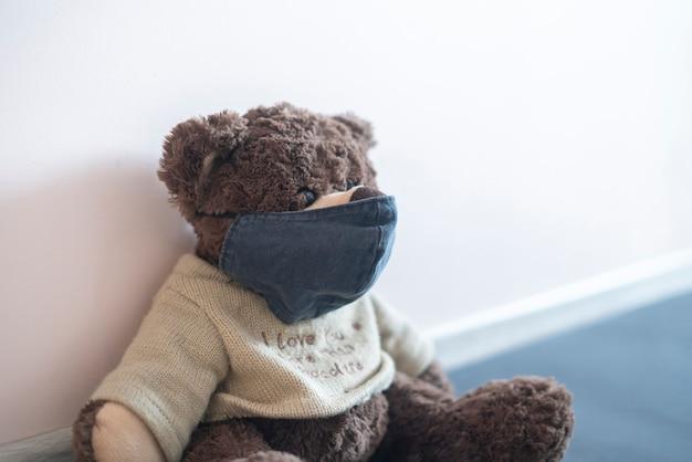 Een speelgoedteddybeer met een beschermend gezichtsmasker, concept van coronavirusepidemie