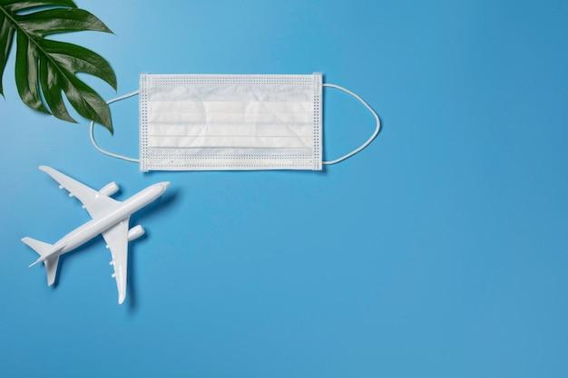 Een speelgoedvliegtuig met medisch masker om virus en stof te beschermen. reis- en beschermingsconcept.