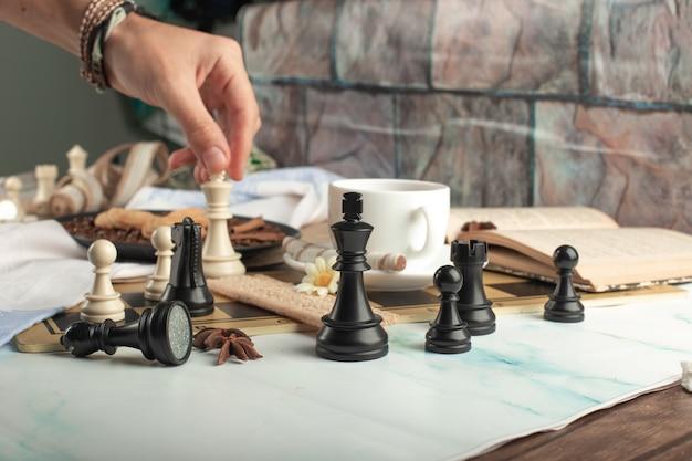 Een speler die schaak op de tafel speelt