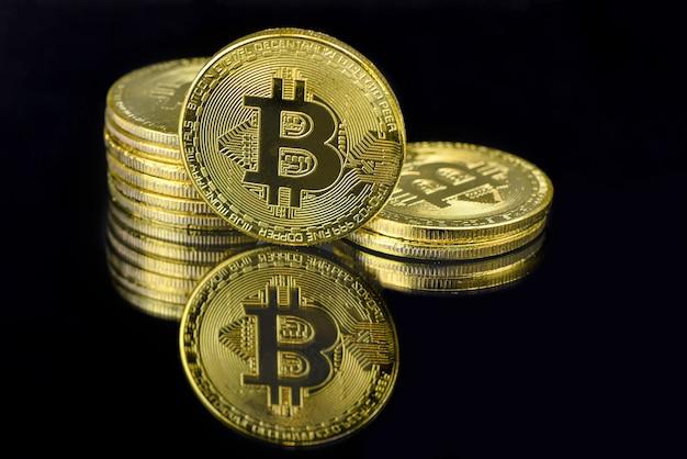Een spiegelbezinning van gouden btc-muntstukken die op zwarte achtergrond worden geïsoleerd