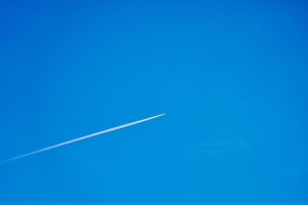 Een spoor vanuit het vliegtuig in de blauwe heldere lucht.