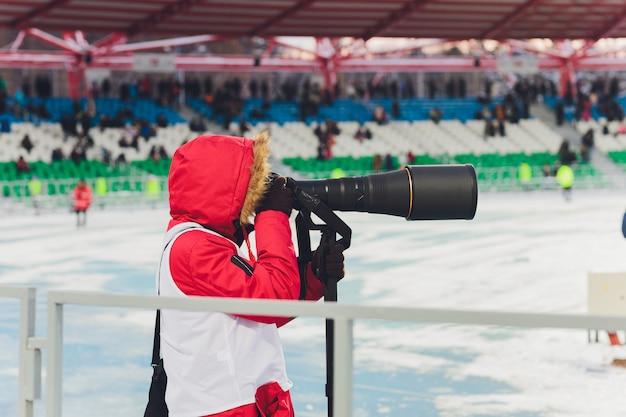Een sportfotograaf die bij een voetbalspel werkt.