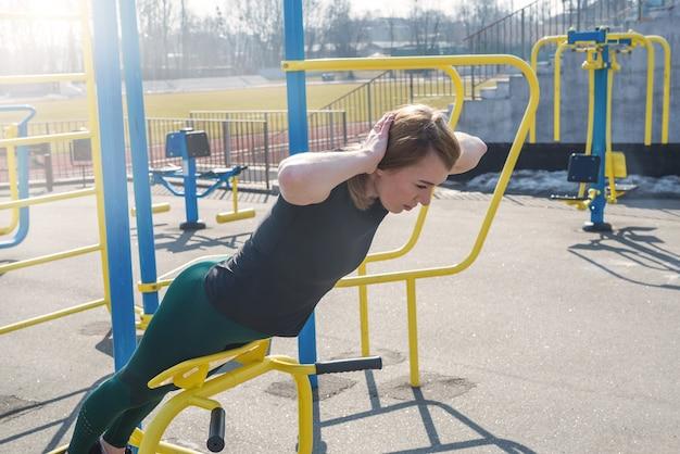 Een sportief meisje schudt de pers op een simulator in de frisse lucht, haar handen achter haar hoofd gevouwen. sportconcept, levensstijl.