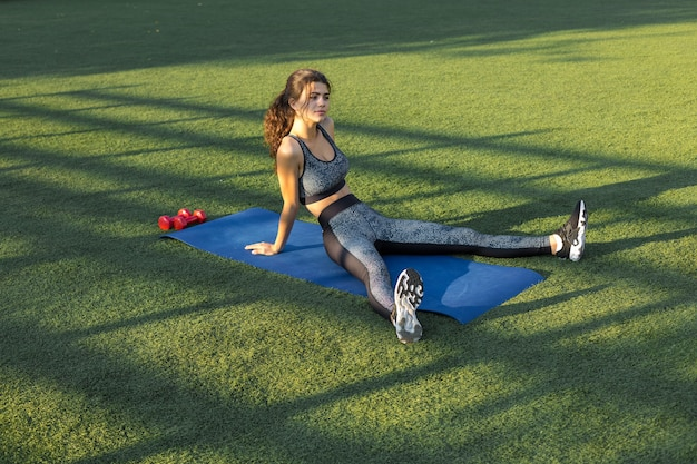 Een sportief slank meisje in een legging en een top staat bij een betonnen muur met een trainingsmat